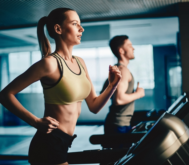 41623520 – active young woman and man running on treadmill in gym